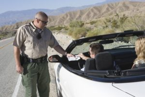 Pima County Sheriff's Deputy or Tucson Police Officer examines papers for bench warrant at traffic stop in Tucson Arizona.